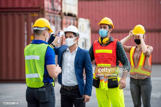 coronavirus temperature check point. group of cargo container workers using medical digital thermometer for self check tempreature at working area for prevention infection, outbreak of coronavirus. - temperature checkpoint stock pictures, royalty-free photos & images