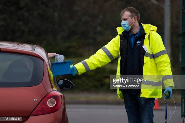 Coronavirus test is handed through a car window to a member of staff at a temporary coronavirus testing centre at Stoke Gifford park and ride on...