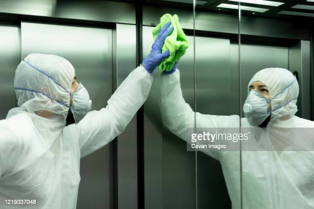 coronavirus. worker disinfecting hospital elevator to avoid contagion. - avoidance stock pictures, royalty-free photos & images