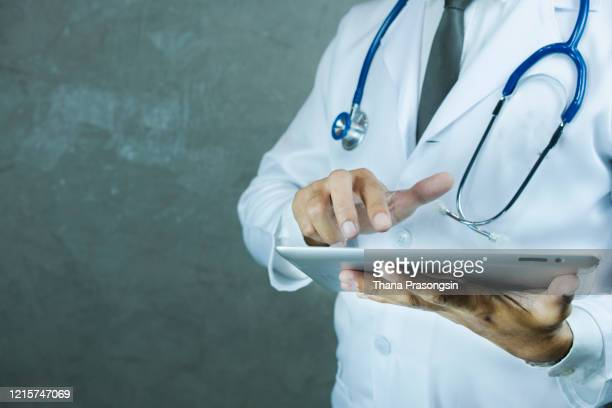coronavirus-doctor holding tablet with futuristic hud screen tablet. covid-19 - doctor stock pictures, royalty-free photos & images