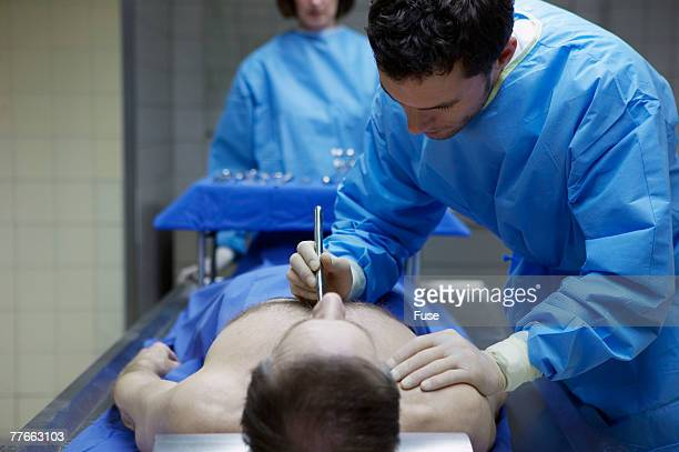 coroner examining body in morgue - female autopsy photos stock photos and pictures