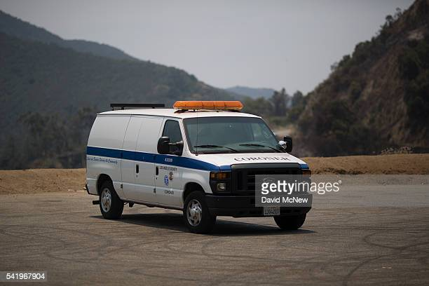 Coroner van is seen at the site of a fatal crash that is believed to have started the San Gabriel Complex Fire in the Angeles National Forest on June...