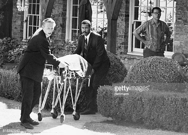 Coroner's office personnel wheel the body of film actress Sharon Tate from her home in Bel Air California August 9th after she and four others were...