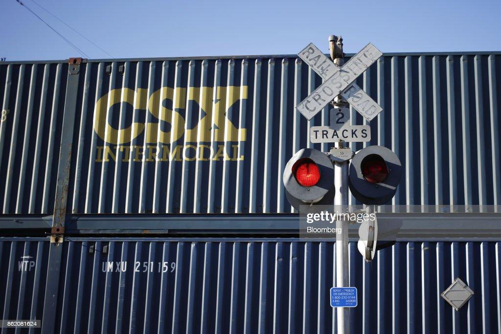 Corp  intermodal container train passes a railroad crossing