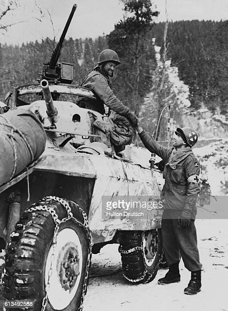Corporal Ancel Casy shakes the hand of Private Alfred Gernhardt as the First and Third U.S Armies link-up near Houffalize in January 1945.