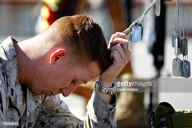 Corporal Brian Reimers a combat correspondent attached to the 1st Battalion 25th Marines holds the dog tags of his fallen companions as the Marines...