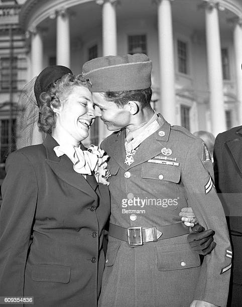 Corporal Desmond T Doss Lynchburg VA a conscientious objector receives a kiss from his wife after ceremonies in the White House gardens during which...