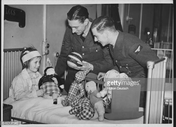 Corporal HP Wren and Aircraftman E Ainge of the Royal Air Force deliver Christmas presents to Joyce Hindley in a London hospital