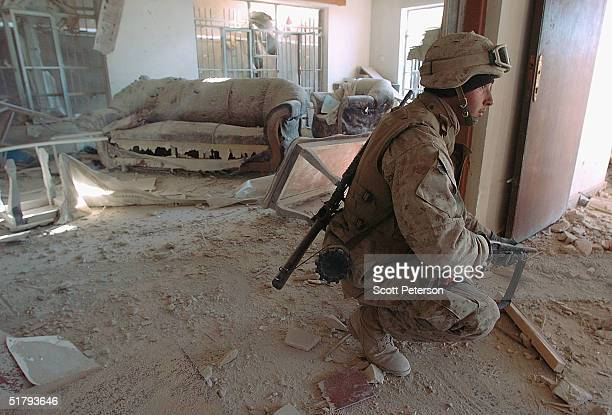 Corporal Jason Hampton stands guard as US Marines of the 1st Light Armored Reconnaissance company as part of 1st Battalion 3rd Marines clear and...