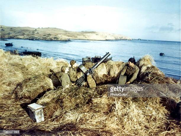 Corporal John Lego Pfc Floyd Carl and Pfc Angelo Terrasi are shown manning this machine gun to cover landing operations at Machitka Adak Island in...