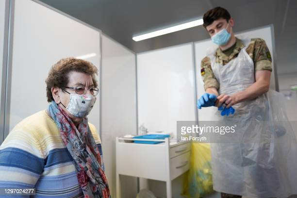 Corporal Lee Cook from 5 Medical Regiment speaks to Dorothy Wood before she receives the AstraZeneca/Oxford University covid-19 vaccination at the...