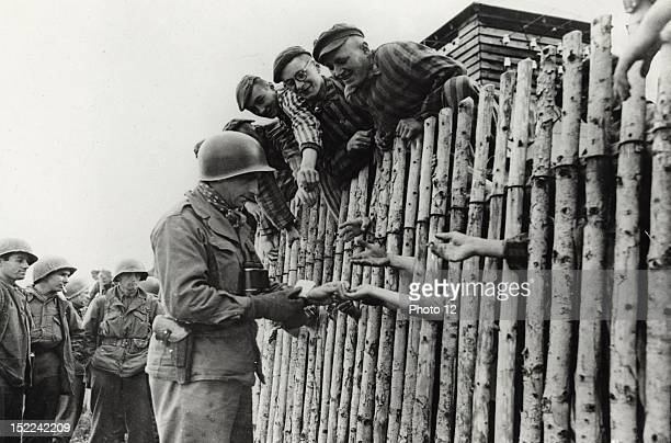 A Corporal member of the 45th Infantery Div 7th US Army distributes his last package of cigarets to liberated prisoners clamoring at a stockade of...