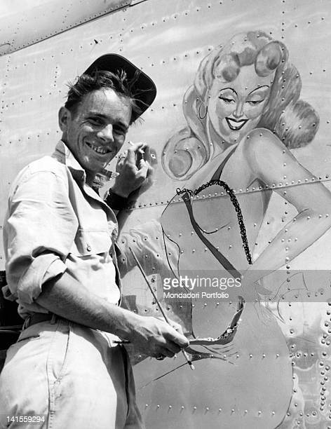 A US Corporal painting a pinup on the fuselage of a plane Italy July 1944