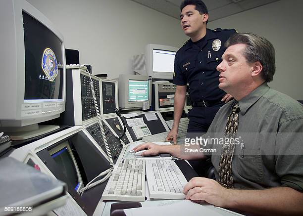 Corporal Ralph Martinez left is assisted by Pat Cronan with the computer networking system in the dispatch center for the Ventura police and fire...