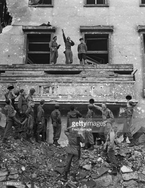Corporal Russell M Ochwad of Chicago playing the part of Adolf Hitler makes the Nazi salute on the balcony of the Reich Chancellery in Berlin from...