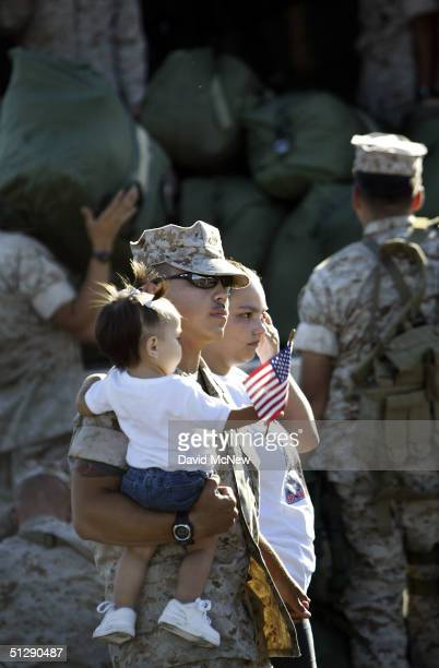 Corporal Terrence Van Doorn walks past Marines loading their sea bags onto a truck with his wife Staphanie Van doorn and one-year-old daughter...