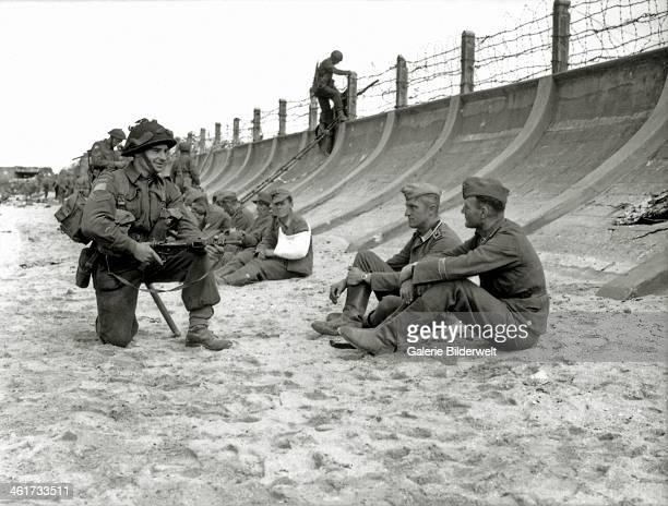 Corporal Victor Deblois from the 3rd Canadian Infantry Division crouching weapon in hand before two German prisoners sitting at the foot of the...