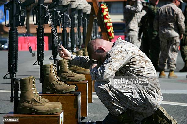Corporal William Ward a combat correspondent with the 1st Battalion 1st Marines holds the dog tags of fallen companions as the Marines of Regimental...