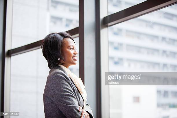 Corporate African female executive looking out the buidling window