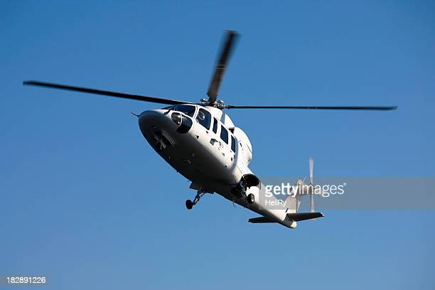 corporate helicopter in flight - helicopter rotors stock photos and pictures
