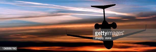 Avion privé d'entreprise avion volant au coucher du soleil