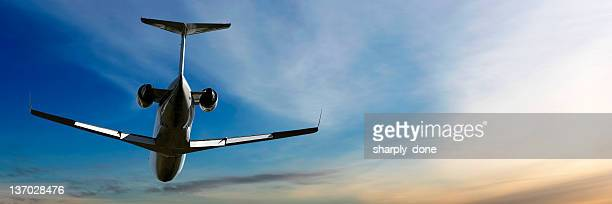 corporate jet airplane flying at dusk
