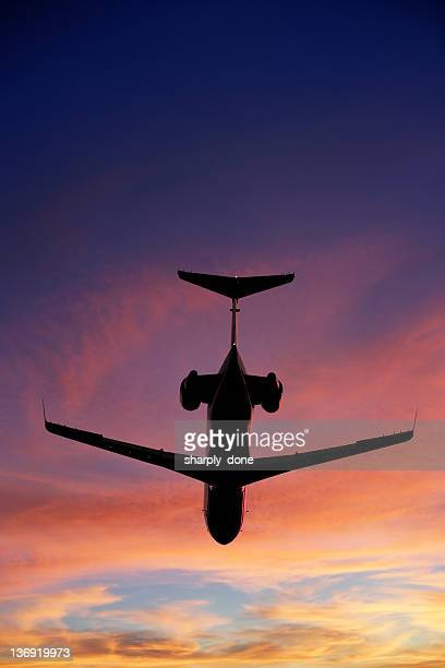 corporate jet airplane flying at sunset