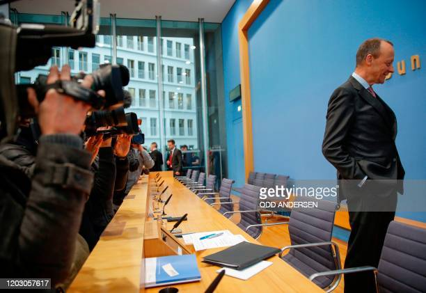 Corporate lawyer and former CDU parliamentary group leader Friedrich Merz talks to a media officer as photographers take pictures as he arrives to...