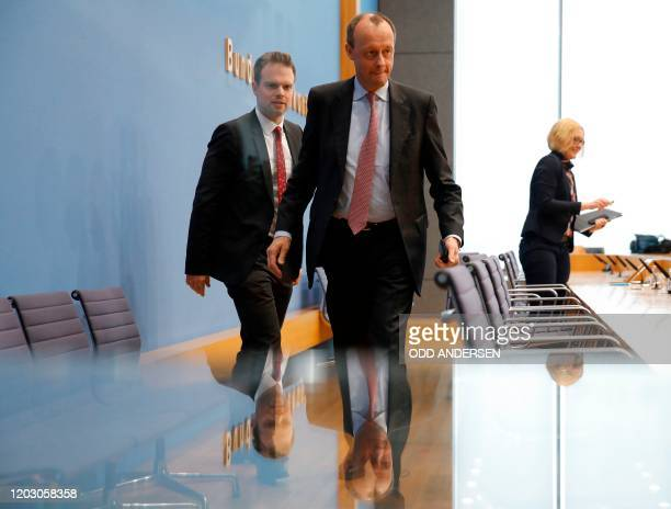 Corporate lawyer and former CDU parliamentary group leader Friedrich Merz leaves with his spokesman Armin Peter after addressing a press conference...