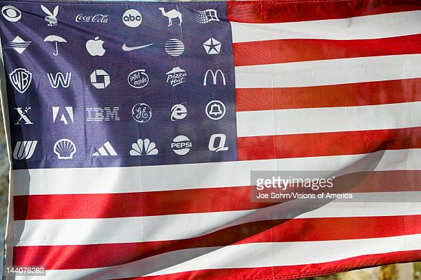 Corporate logos in place of stars on the American flag symbolize allegiance to and dominance of Corporate America