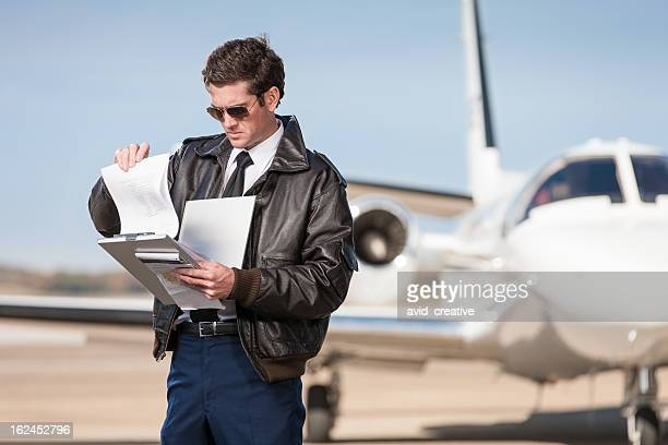 corporate pilot checking flight plan - bomber jacket stock pictures, royalty-free photos & images