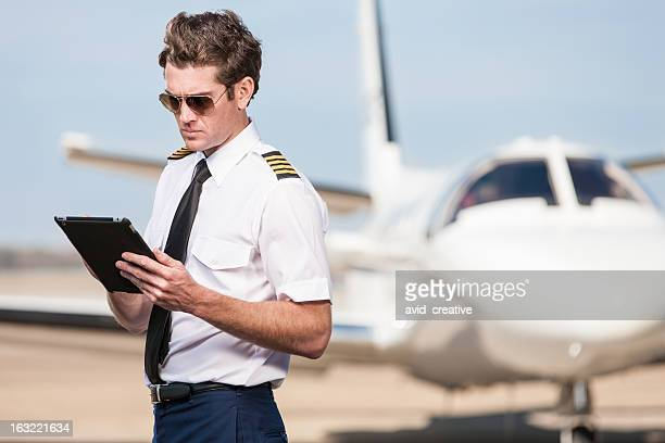 corporate pilot using electronic tablet - team captain stock pictures, royalty-free photos & images