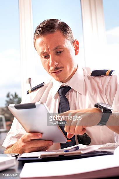 corporate pilot using electronic tablet - epaulettes stock pictures, royalty-free photos & images