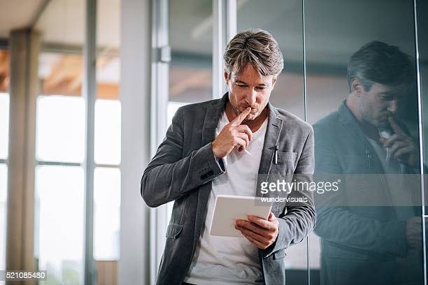 Corporate professional executive concentrating on a presentation on his tablet.
