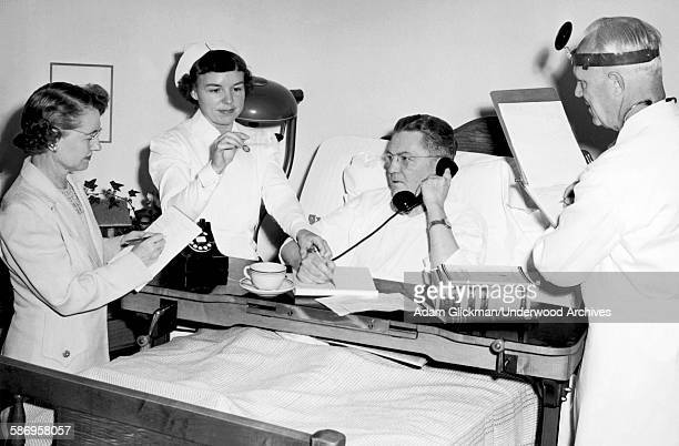 Corporate secretary takes notes as her bedridden boss is tended to by a nurse and a doctor, late 1940s.