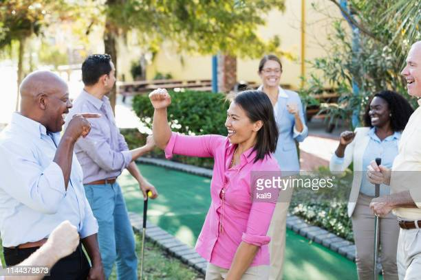 corporate team building, playing miniature golf - miniature golf stock photos and pictures