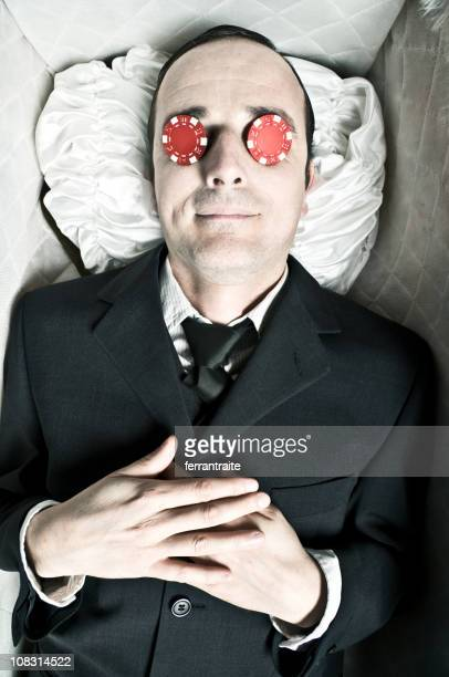 Corpse in coffin with poker chips on eyes