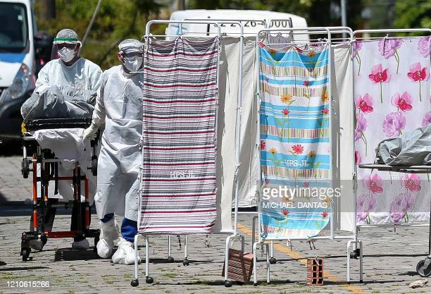 TOPSHOT A corpse of a COVID19 coronavirus victim is moved by medical staff in protective suits into a refrigerated area of the Joao Lucio Hospital in...