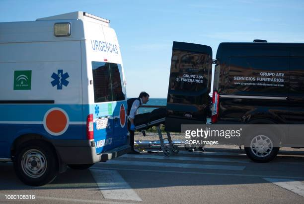 A corpse of a migrant seen carried into a mortuary van after arriving on the beach on a dinghy with a group of migrants A dinghy with migrants and...