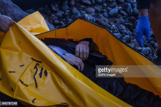 Corpse of a refugee being put into a body bag. The corpse belong to a boat that sank the previous night off the Greek coast. Ten of thousands of...