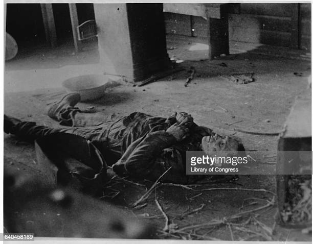 A corpse probably that of an inmate lies on the floor of a concentration camp near Leipzig Germany April 1945 | Location near Leipzig Germany
