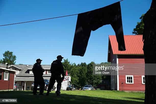 Correction officers search around a home as the manhunt for convicted murderers Richard Matt and David Sweat continues on June 26 2015 in Chasm Falls...