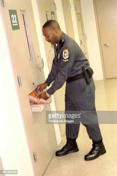 corrections officer handcuffing inmate in cell - prison guard stock pictures, royalty-free photos & images