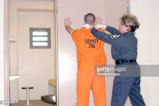 corrections officer searching inmate - prison guard stock pictures, royalty-free photos & images