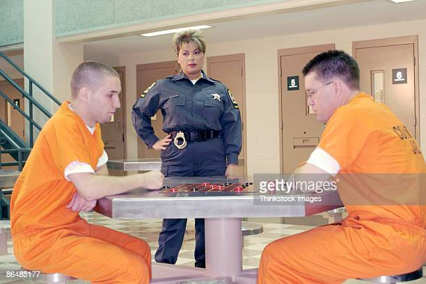 corrections officer watching inmates playing checkers - prison guard stock pictures, royalty-free photos & images