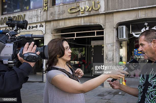 A correspondent for Syrian state television interviews a man in the streets of Damascus Syria Sepetember 19 2012 While smoke rises in the background...