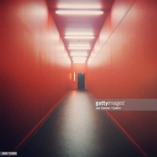 Corridor Amidst Red Wall In Building