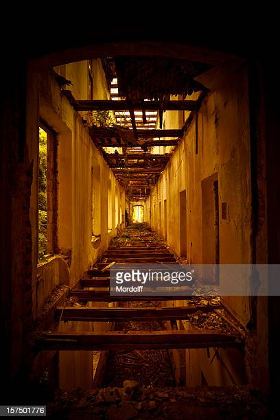 Corridor with broken floor and ceiling in abandoned house