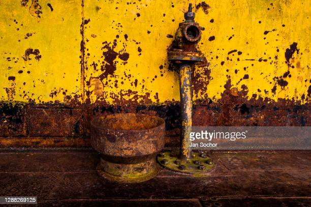 Corroded water pipe is seen on the deck of an old gold dredge anchored in the Atrato river on October 12, 2019 in Quibdó, Colombia. A gold dredge is...