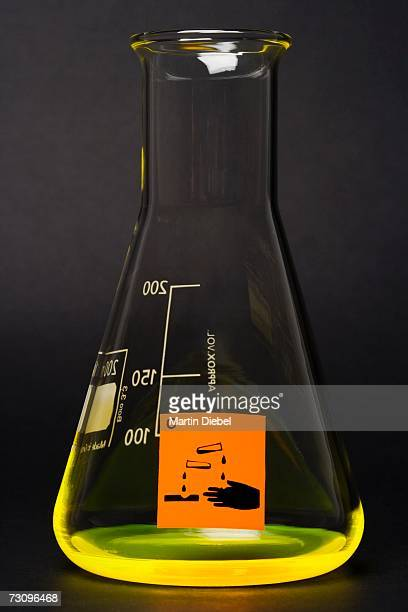 ?corrosive? label on conical flask containing yellow liquid - acid warning stock photos and pictures